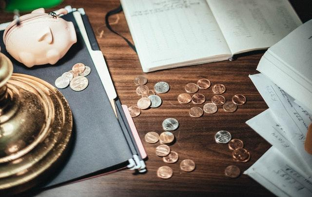 A piggy bank and coins on the table representing a problem of how to choose between a house and a condo in Tucson.